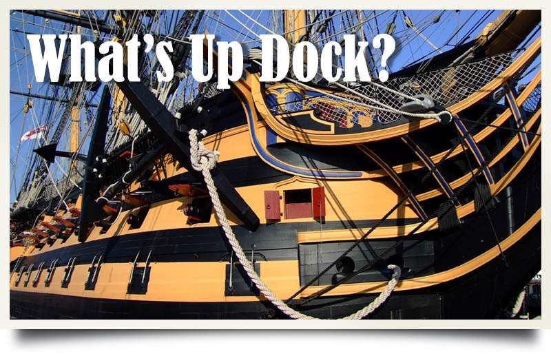 Postcard of HMS Victory with caption 'What's Up Dock?'.
