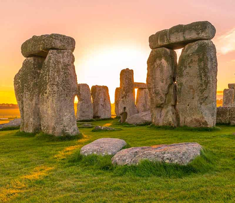 The sun rising behind the standing stones at Stonehenge.